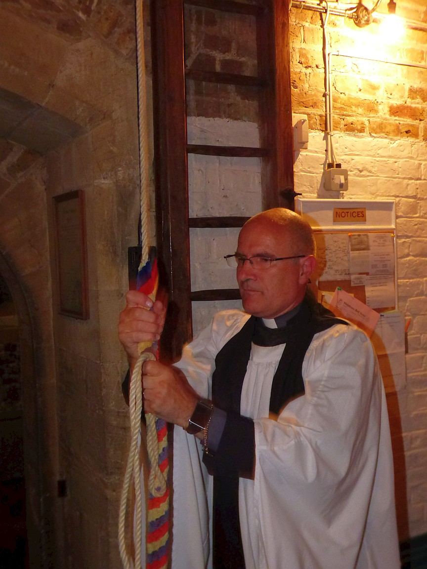 Vicar ringing bell as his symbolic first act